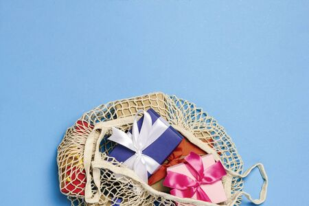 Gifts in a fashionable bag for shopping on a blue background. Gift shopping concept, discount, sale. Flat lay, top view.