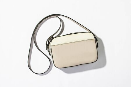 Womens fashion bag with a long handle on a white background. Natural light, modern trend, minimalism. Flat lay, top view.