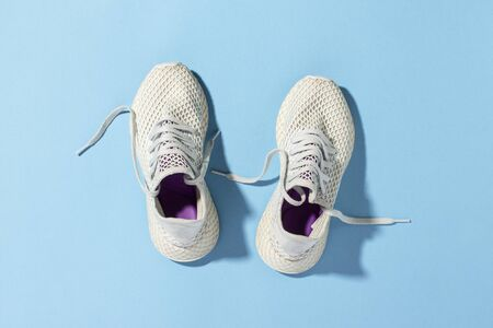 White sneakers under morning sunlight on a blue background.Jogging, running, fitness, cross fit, hard workout. Morning run. Banner. Flat lay, top view. Banco de Imagens