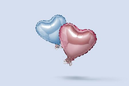 Flying Blue and Pink air balloons in the shape of a heart on a pink background. Love concept, valentines day. Banner. Flat lay, top view.