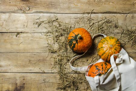 Pumpkins in a bag for shopping on a wooden background. Harvest concept, autumn, Halloween eve. Banner. Flat lay, top view.