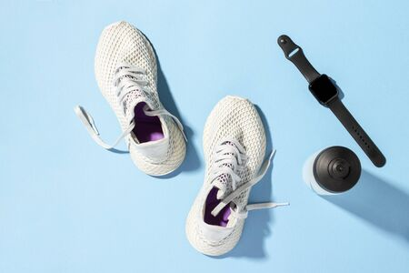 Fitness tracker, White sneakers and a bottle of water under morning sunlight on a blue background.Jogging, running, fitness, cross fit, hard workout. Morning run. Banner. Flat lay, top view. Stock Photo