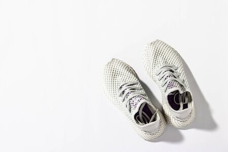 Sneakers on a white background under the morning sun. The concept of running, fitness, cross fit. Morning running. Natural light. Flat lay, top view. Banco de Imagens