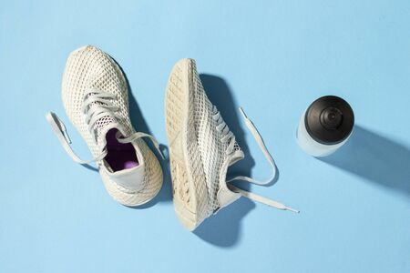 White sneakers and a bottle of water under morning sunlight on a blue background.Jogging, running, fitness, cross fit, hard workout. Morning run. Banner. Flat lay, top view.
