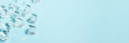 Ice cubes with water on a blue background. Ice concept for drinks. Banner. Flat lay, top view.