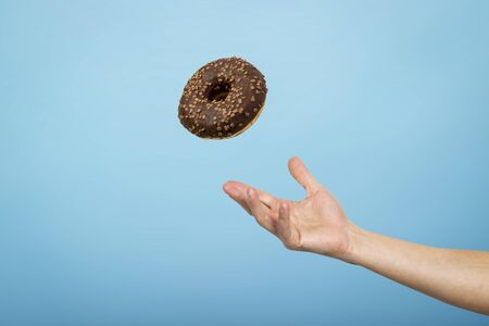 Hand catch a donut with chocolate icing. Blue cardboard background. Concept of baking, handmade. Flat lay, top view.