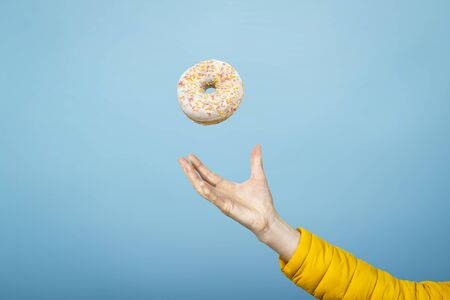 Hand catch a donut with icing. Blue cardboard background. Concept of baking, handmade. Flat lay, top view. Stockfoto