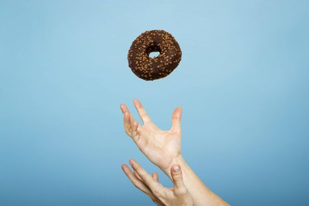 Hands catch a donut with icing. Blue cardboard background. Concept of baking, handmade. Flat lay, top view.