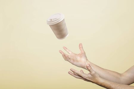 hands catch a cardboard glass on a light cardboard background. Concept of coffee, tea, advertising, coffee breaks. 写真素材