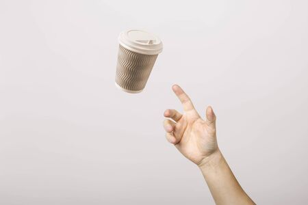 hand catches a cardboard glass on a light cardboard background. Concept of coffee, tea, advertising, coffee breaks. 写真素材