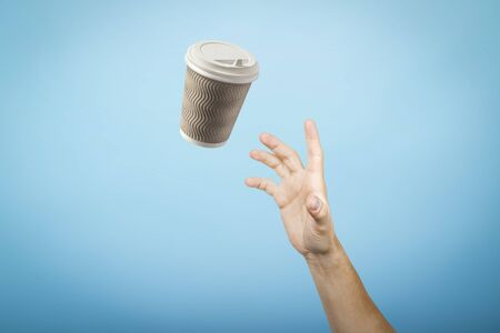 hand catches a cardboard glass on a blue cardboard background. Concept of coffee, tea, advertising, coffee breaks. 写真素材