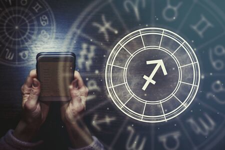 Female hands are holding a phone and an astrological circle with the zodiac sign Sagittarius against the background of the starry sky. Horoscope app.