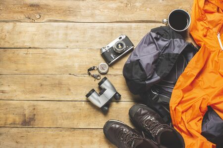 Boots for a trail, jacket, backpack, hiking gear on a wooden background. The concept of hiking, tourism, camp, mountains, forest. Banner. Flat lay, top view.