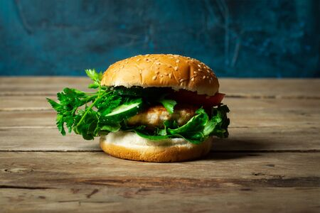 Fresh home-cooked appetizing tasty burger with chicken on wooden table.