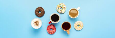Tasty donuts and cups with hot drinks, coffee, cappuccino, tea on a blue background. Concept of sweets, bakery, pastries, coffee shop, meeting, friends, friendly team. Banner. Flat lay, top view.