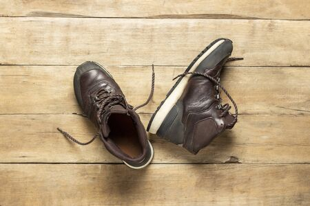 Hiking boots on a wooden background. The concept of hiking, tourism, camp, mountains, forest. Banner. Flat lay, top view.