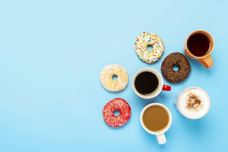 Tasty donuts and cups with hot drinks on a blue background. Concept of sweets, bakery, pastries, coffee shop, friends, friendly team. Flat lay, top view.