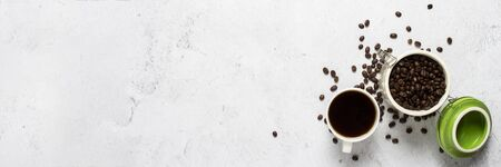 cup with coffee, a can of coffee beans and coffee beans are scattered on a concrete background. Banner. Concept of fresh coffee, breakfast, plantation. Top view, flat lay.