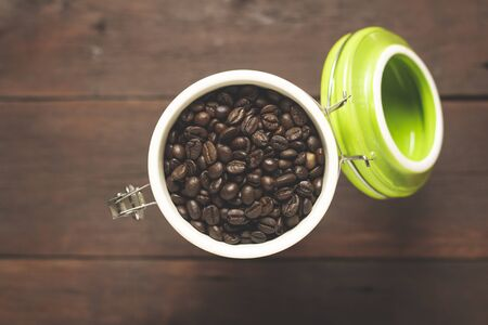 can with grains of coffee on a wooden table. Banner. Concept of coffee, plantation, processing, collection. Top view, flat lay.