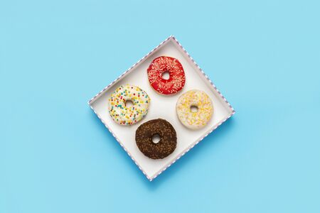 Tasty donuts in a box on a blue background. Concept of sweets, bakery, pastries, coffee shop. Banner. Flat lay, top view.