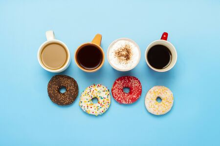 Tasty donuts and cups with hot drinks, coffee, cappuccino, tea on a blue background. Concept of sweets, bakery, pastries, coffee shop, meeting, friends, friendly team. Flat lay, top view. Archivio Fotografico