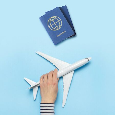 Female hand holds an airplane and passports on a blue background. Concept flight, tickets, booking, flight search, travel. Banner. Flat lay, top view.