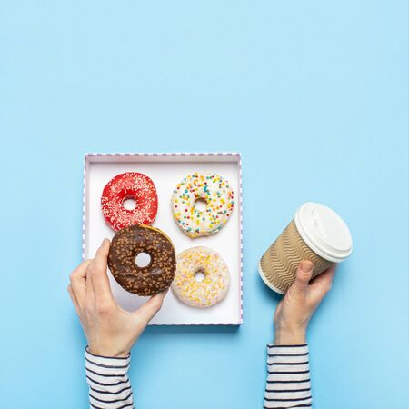Female hands are holding a donut and a cup of coffee on a blue background. Concept confectionery store, pastries, coffee shop. Banner. Flat lay, top view. Archivio Fotografico