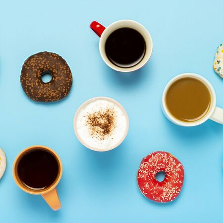 Tasty donuts and cups with hot drinks, coffee, cappuccino, tea on a blue background. Concept of sweets, bakery, pastries, coffee shop, meeting, friends, friendly team. Square. Flat lay, top view.