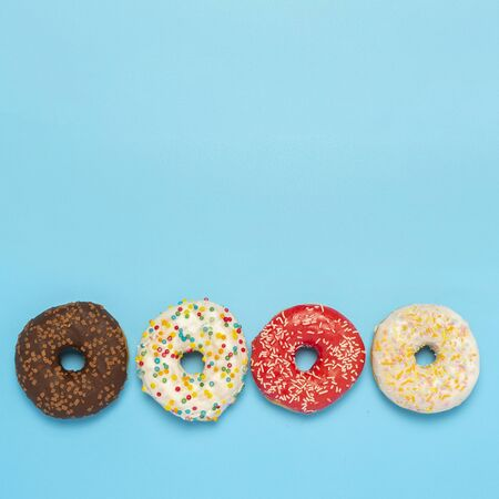 Tasty donuts of different types on a blue background. Concept of sweets, bakery, pastries. Square. Flat lay, top view.