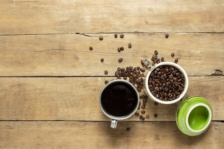 cup with fresh coffee and a can with coffee grains, coffee beans are scattered on a wooden table. Banner. Coffee concept, plantation, processing, collection. Top view, flat lay. Reklamní fotografie - 150121753