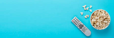 Bowl with popcorn and remote control for TV on a blue background. Concept home theater, movie, leisure. Flat lay, top view.