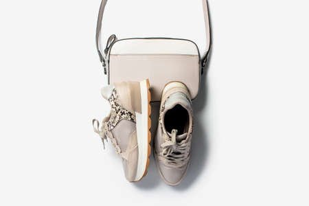 Women's beige sneakers and cross-body bag on a light background. Flat lay, top view.