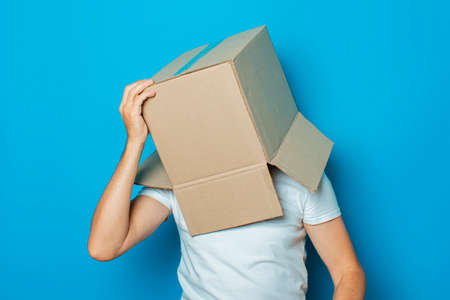 Young man in a white T-shirt with a cardboard box on his head makes a gesture with his hands on a blue background.