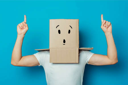 Young man in a white T-shirt with a cardboard box on his head on a blue background. Makes a hand gesture Strength and Power, bodybuilding, sport.