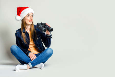 Smiling young woman sitting in santa claus hat holding binoculars on a light background