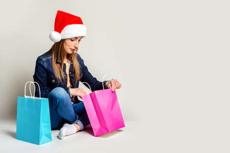 Young woman sits on the floor in santa claus hat, looks in a package with purchases on a light background
