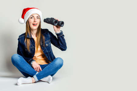 Friendly young woman is sitting in santa claus hat, holding binoculars on a light background