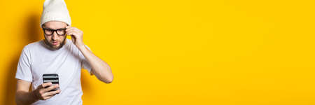 Bearded young man looks at the phone with concentration on a yellow background. Banner
