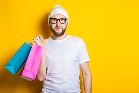 Friendly smiling young man with a beard, in glasses and a hat, holds packages with purchases on a yellow background