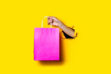 Female hand holds a pink package with purchases on a yellow background.