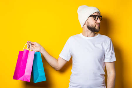 Bearded young man looking away and holding shopping bags on yellow background