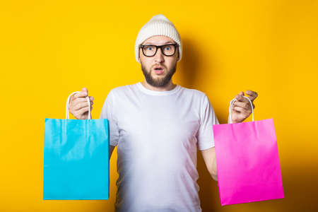 Bearded surprised young man with glasses holding two shopping bags on yellow background