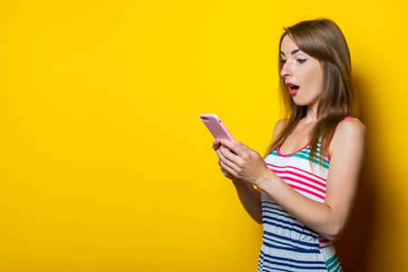 Surprised shocked young girl in a striped dress holds a telephone on a yellow background. 免版税图像