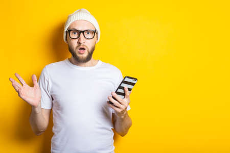 Surprised shocked young man with beard holding phone on yellow background 免版税图像