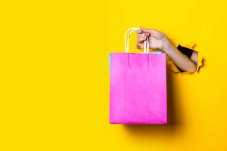 Female hand holds packages with purchases on a yellow background. 免版税图像