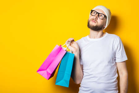 Young man with beard looking up and holding shopping bags on yellow background 免版税图像
