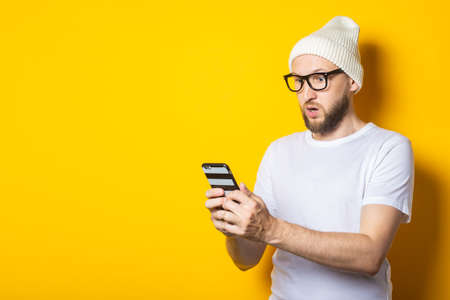 Bearded young man in a hat and glasses looks surprised in surprise at the phone on a yellow background 免版税图像
