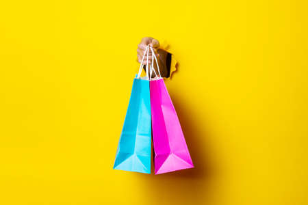 Female hand holds a pink and blue shopping bag on a yellow background.
