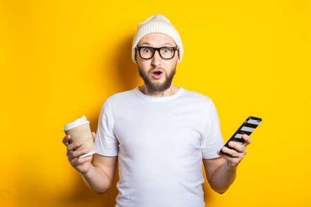 Surprised bearded young man with cardboard glass with coffee, holding phone on yellow background