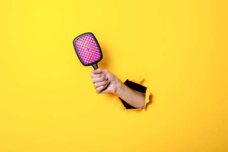 Female hand holds a large hairbrush on a yellow background. Hair accessories.
